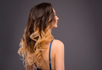 Woman with Long Healthy Colorful Ombre Wavy Hair. Close Up of Hairstyle