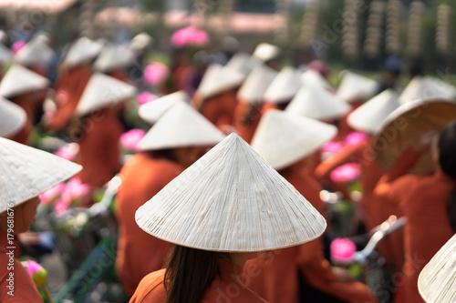 Photo  Vietnamese girls wear traditional long dress Ao Dai cycling on Hanoi street