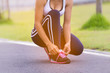 Young woman runner tying shoelaces with copy space,in the park, healthy lifestyle and sport concepts