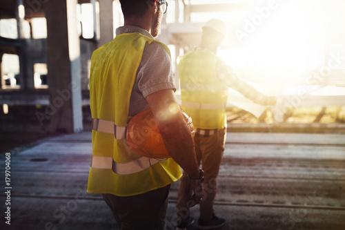 Obraz Portrait of construction engineers working on building site - fototapety do salonu