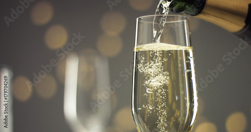 Bottle of sparkling wine with three flute glasses with bubbles floating up on gray backgrounds with Christmas lights