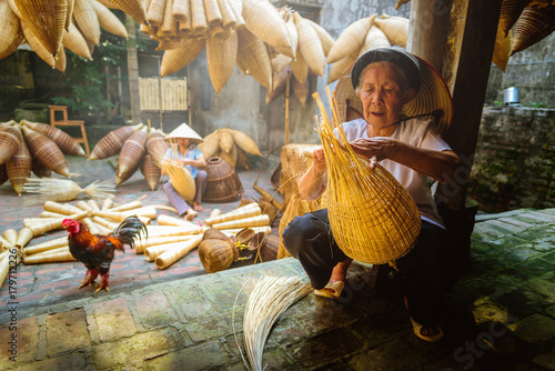 Fotografie, Obraz  Vietnamese fishermen are doing basketry for fishing equipment at morning in Thu Sy Village, Vietnam