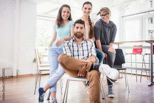 Fotografía four co-workers wearing casual clothes during work in a modern hub for freelance