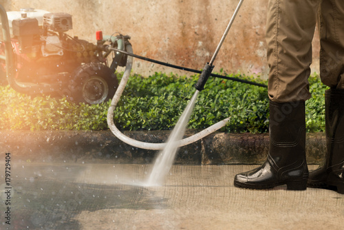 High pressure deep cleaning..Worker cleaning driveway with gasoline high pressure washer ,professional cleaning services. #179729404