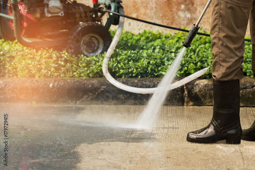 High pressure deep cleaning. .Worker cleaning driveway with gasoline high pressure washer ,professional cleaning services. #179729415