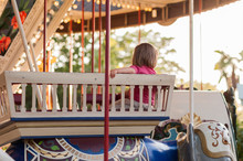 Child On A Carousel At A Carnival Or Festival At Sunset. Decorative Ornate Elephant, Animals At An Amusement Park.