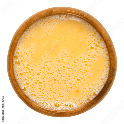 Raw scrambled eggs in wooden bowl. Yolk and white are stirred together and ready for further processing. Used for pancakes, omelettes or for breading. Macro food photo close up from above over white.