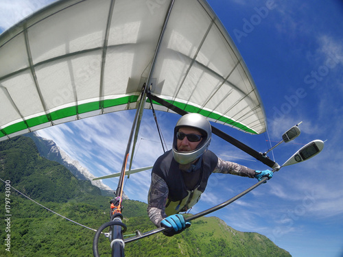 Fotografía  Hang glider pilot soaring the thermal updrafts above green mountain hills