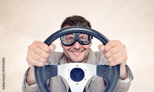 Zdjęcie XXL Brodaty szczęśliwy mężczyzna w eleganckich gogle z kierownicą na tle, kierowca pojęcie