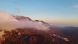 Camera moving through clouds in mountains. Fantastic dreamy sunrise on top of rocky mountain with view into misty valley.