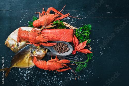 Plakat Owoce morza. Ryby Vomer, homar, łosoś. Na drewnianym tle. Widok z góry. Wolne miejsce na tekst.