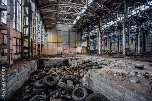 Autocollant pour porte Les vieux bâtiments abandonnés Junk of tires in abandoned industrial hall. Former Voronezh excavator factory