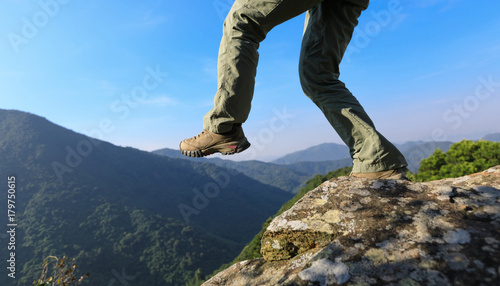 brave woman hiker walking to the cliff edge on top of mountain Canvas Print