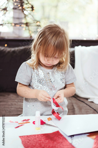 3 Year Old Making A Christmas Garland With Red Glitter Paper Lifestyle Image