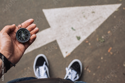 Traveler holding compass in the hand making choice in what direction to go