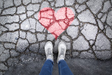 Person Stands On Cracked Asphalt Floor With Painted Red Heart Symbol. Personal Perspective Used.
