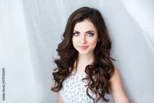 Fotografie, Obraz  Beautiful brunette with long curly hair.