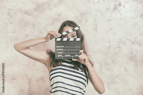 Woman with movie clapper board over face audition concept Wallpaper Mural