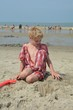 Kind am Strand spielt mit Sand, Meer und viele Personen im Hintergrund