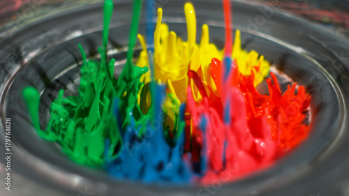 Photo  Rainbow paint splashing upwards in silver bowl