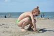 Mädchen gräbt Loch mit ihren Händen am Sandstrand vor dem Meer