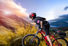 Strong Woman Riding Moutain Bike Upon The Hill With Strong Windy Impact Through The On The Moutain, River And Moutain In Background