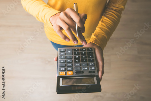 Fotografía  Woman using a calculator with a pen in her hand
