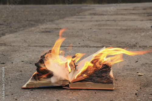 Fotografiet  book with burning pages on a concrete surface