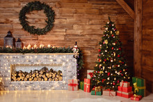 Photo Of Interior Of Room With A Wooden Wall, Wreath And Garlands, Christmas Tree, Fireplace With Firewood. Christmas Atmosphere. Home Comfort