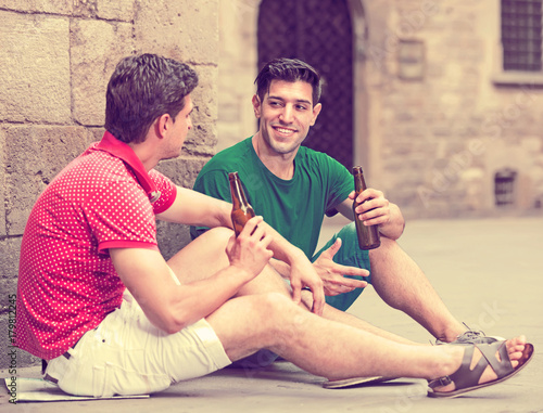 Photo joyous male fans are drinking beer and talking about football outdoor in Barcelo