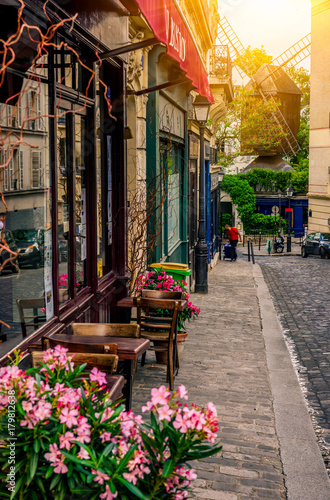 Ingelijste posters Parijs Cozy street with tables of cafe and old mill in quarter Montmartre in Paris, France