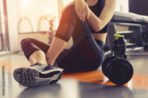 Deurstickers Fitness Woman exercise workout in gym fitness breaking relax holding protein shake bottle after training sport with dumbbell and healthy lifestyle bodybuilding.