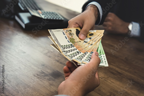 Fotomural  Businessman receiving money, South Korean WON currency bills, hand to hand