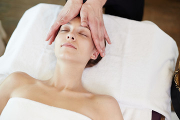 Fototapeta na wymiar Above view portrait of young woman enjoying face lifting massage lying with eyes closed in SPA center and relaxing