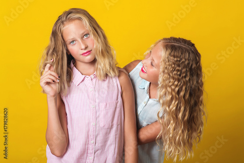 Photo  Funny girls twins have fun together on yellow background.