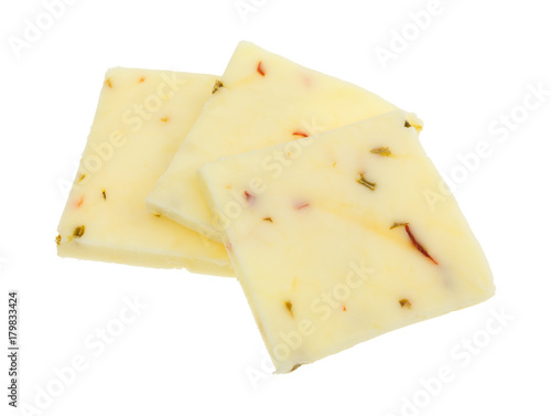 Three squares of fresh pepper jack cheese isolated on a white background.