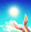 Bright sun between two hands over blue sky showing freedom or solar power concept