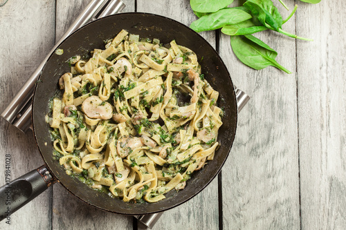 Cuadros en Lienzo  Tagliatelle pasta with spinach and mushrooms on a pan.