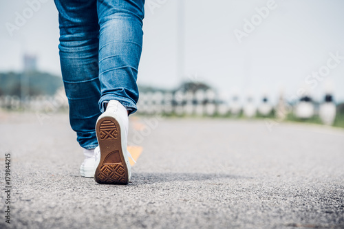 Close up woman wear jean and white sneaker walking forward on highway road in su Canvas Print