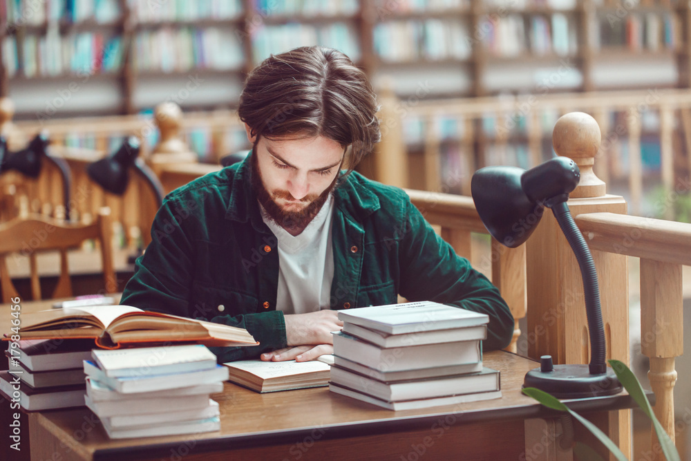 Fototapeta Long hair student man use books for studying to exams before bookshelves in library, education concept