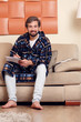 Image of smiling man in home dressing gown with magazine on couch