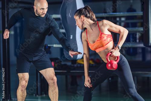Plakat Osobisty trener ćwiczy z kettlebell z kobietą w gym