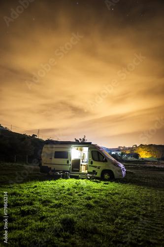Fotografía Fotografía nocturna de una autocaravana aparcada sobre un prado