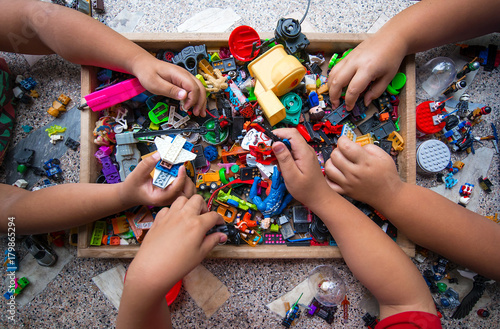 The hands of many children who are playing toys together. Tableau sur Toile