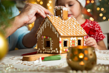 Father and adorable daughter in red hat building gingerbread house together. Beautiful decorated room with lights and Christmas tree, table with candles and lanterns. Happy family celebrating holiday.