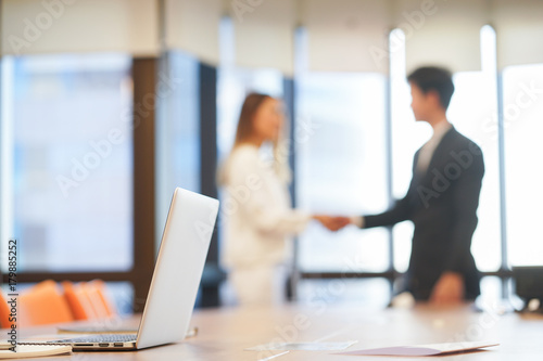 Photo  close up on laptop with blurred businesspeople hand shake together for success m