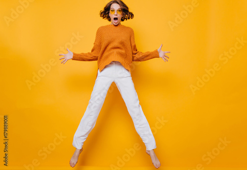 Photo  Full-length portrait of funny woman in white pants fooling around on yellow background
