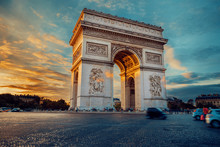 Famous Paris Avenue Champs-Elysees And The Triumphal Arch, Symbol Of The Glory On Bright Sunny Day With Cloudy Sky. Iconic Touristic Landmark And Romantic Travel Destinations In France. Long Exposure