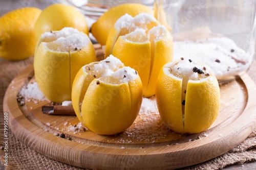Fotografia, Obraz  Preserved lemons with salt on a wooden board