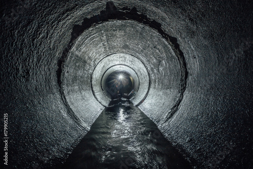 Photo sur Toile Canal Underground river flowing in round concrete sewer tunnel. Sewage collector